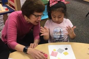 Illinois Art Station Laura Berk founding donor with IAS child making art
